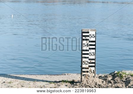 Black and white water level meter indicator on the shore near the river flow for safety of the city against flood