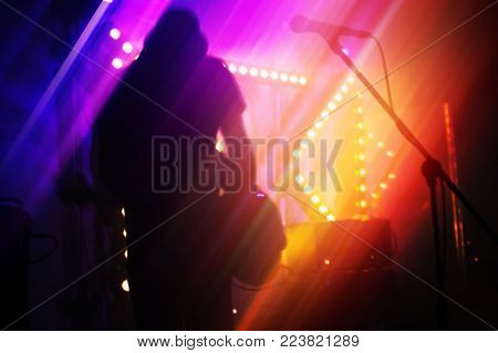 Bright colorful blurred rock music abstract background, bass guitar player on a stage