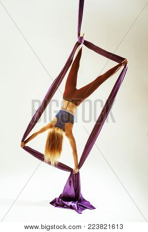 Aerial acrobat is making rectangle element hanged on fabric