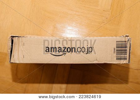 PARIS, FRANCE - APR 9, 2017: Cardboard box from Amazon.co.jp with distinct online retailer logotype insignia on wooden floor