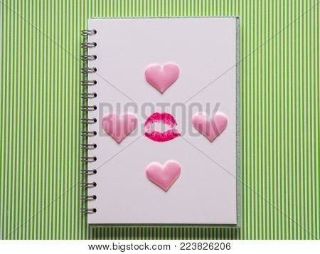 White page with girlish pen and lipstick kiss on green background. Valentine's day, girl's blog concept