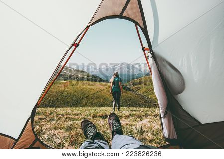 Travel camping couple view from tent entrance woman walking in mountains man feet relaxing inside Lifestyle concept adventure summer vacations outdoor