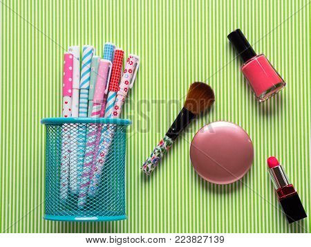 Girlish flatlay with pastel pens and makeup accessories. Girl's blog concept