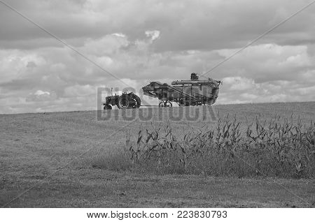 DALTON, MINNESOTA, Sept 8, 2017: A Farmall tractor and old vintage Case threshing machine are silhouetted on a hill at the annual Dalton Threshing Bee farm show in Dalton held each 2nd full weekend in September where 1000`s attend. (black and white)