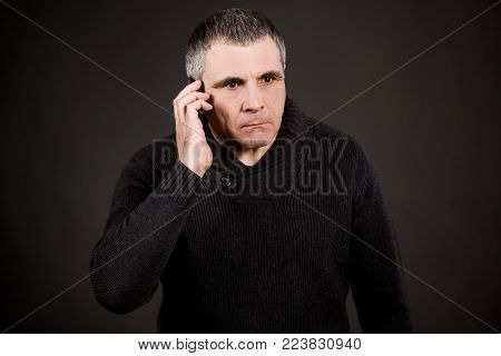 Emotional man himself upset. A man in a dark sweater on a black background. Emotional man himself upset, he pondered and made an important decision.