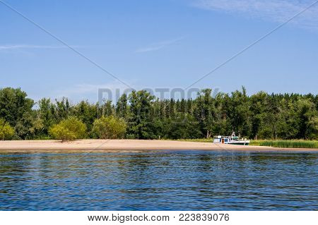 A small river ship is standing in the backwater behind sand braid on the river Volga.