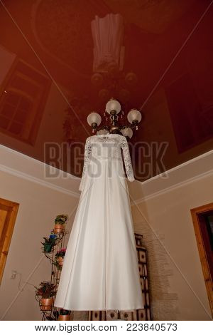 Beautiful wedding dress hanging on the lamp in the room with a shiver in the ceiling. Wedding Morning.