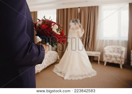 Wedding, bride and groom, first meeting. bridegroom holds wedding bouquet in her hand, bride stands with her back in white classic wedding dress with lace veil.