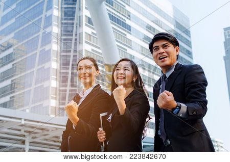 yeah, finally we did it, group of business people in suit screaming showing their strong hands together standing in modern city, successful, support, meeting, partner, teamwork and community concept