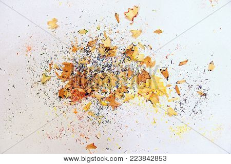Wooden colored pencil sharpening shavings pile on white isolated background