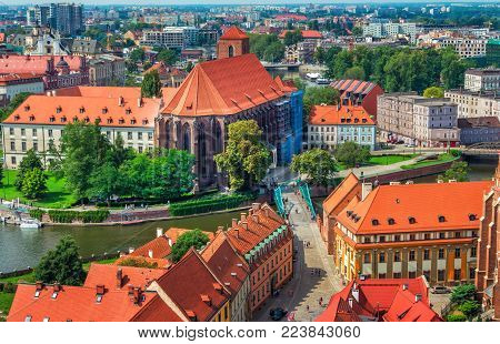 Wroclaw/Poland- August 18, 2017: aerial panoramic cityscape - river Odra, part view of Tumski Island and bridge,  historical and modern buildings, alley, park and green trees summertime, blue sky