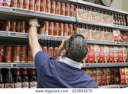 Lisbon, Portugal - August 03, 2017: A man chooses a Portuguese beer Super Bock on the supermarket counter