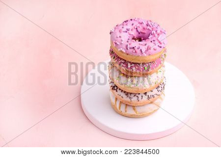 Stack of Delicious Beautiful Donuts on Pink Background Wooden Tray Pink Lilac and White Donuts White Background Vertical Photo