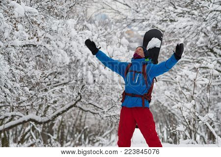 Snowboarder, with open arms, is delighted in the winter forest, stands among the snow-covered trees - anticipation of adventure.  Adventure in wilderness.