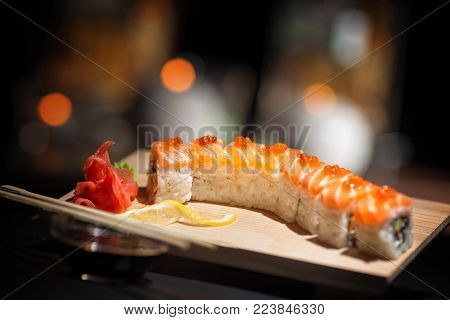 Japanese food. Appetizing sushi on a wooden board. Set nigiri and sushi rolls on wooden board over black background.