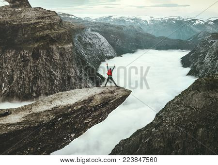 Man jumping on Trolltunga rocky cliff edge in Norway mountains Travel Lifestyle adventure happy emotional concept extreme journey vacations outdoor above clouds