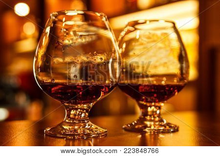 Two glasses of luxury cognac on the wooden table, close-up, warm light