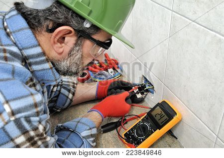 Electrician technician with gloves and safety instruments he measures the voltage of a residential electrical system.