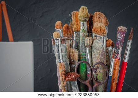 Artistic equipment. The artist's brush and stretcher with a clean canvas on the background of a gray concrete wall in the workshop.
