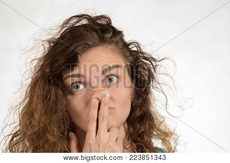Beautiful brunette girl picking at her nose and her stupid face on a white background