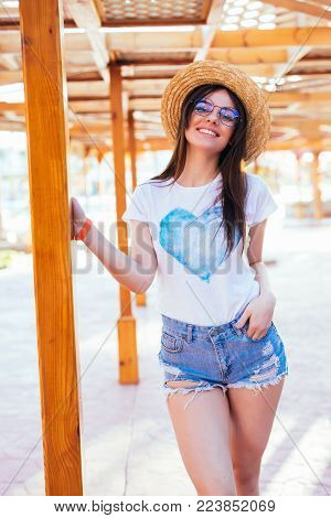 Beauty Woman In Sunglasses And Hat On A Pool Standing Near Chaise Lounge At Summer Time