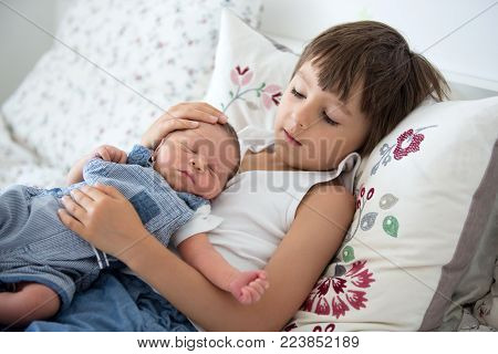 Beautiful Boy, Hugging With Tenderness And Care His Newborn Baby Brother At Home