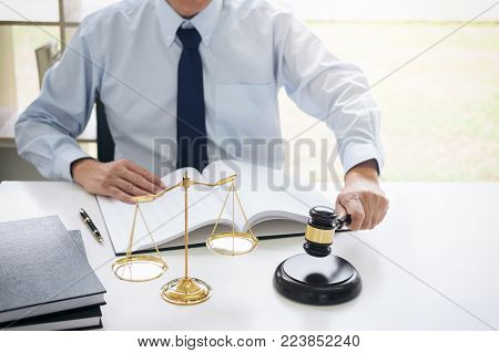 Judge gavel with scales of justice, male lawyers working having at law firm in office. Concepts of law.