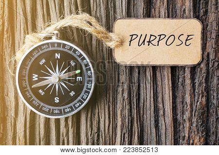 Magnetic compass and paper tag written with PURPOSE text on old wooden background. A concept.