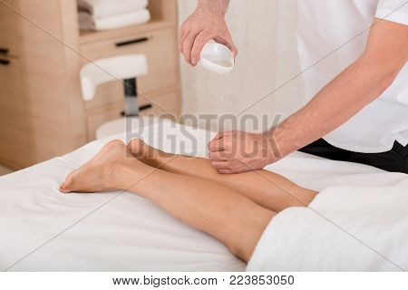 Masseur massaging legs of woman in wellness center. He is pouring out the massage oil on her shin. Close up of his hands