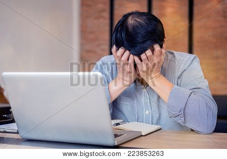 Image of Frustrated stressed business man and graph business with computer laptop in the workplace.