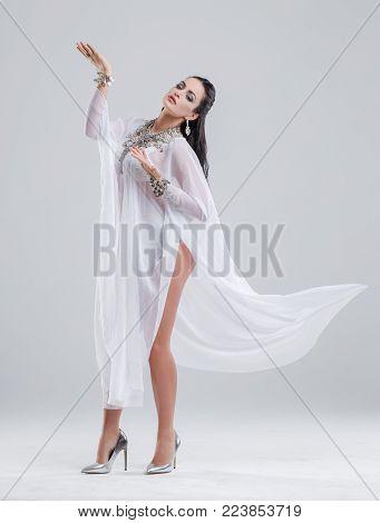 Sensual oriental belly dancer dancing in studio, grey background