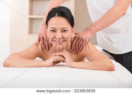 Portrait of satisfied adult female getting a massage in beauty salon. She is lying on the couch with smile while masseur massaging her shoulders