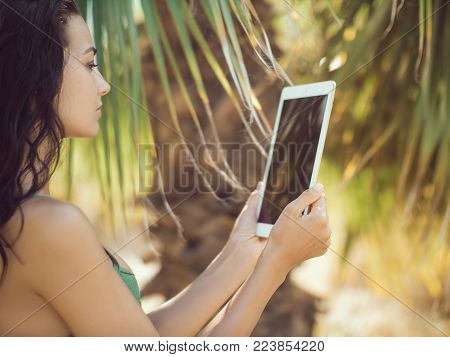 Traveler woman using tablet computer in tropical jungle symbolizing the ability to blend work and rest while working from anywhere. Close-up of sensual young brunette mixed race Asian Caucasian girl wearing swimsuite with wet hair surfing internet or usin