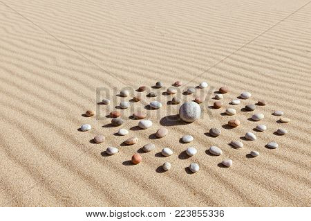 Pattern of colored pebbles in the shape of a circle on clean sand. The concept of serenity and meditation