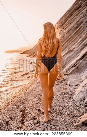 Attractive woman in black bikini walk on beach with warm sunset colors.