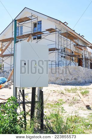 Electric power meter outdoor. House Watt hour Electric meter measurement on passive house wall insulation, repair, plastering, painting, renovation.