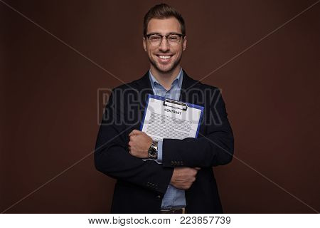 Portrait of cheerful barded businessman holding clipboard with document in arms. Profession concept