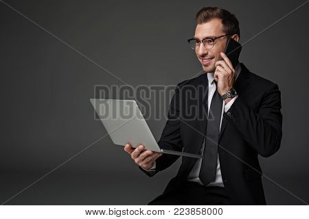 Portrait of happy male telling by mobile while working at laptop. Profession concept