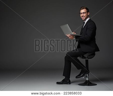 Full length portrait of beaming bearded businessman typing in notebook computer on chair. Profession concept. Copy space