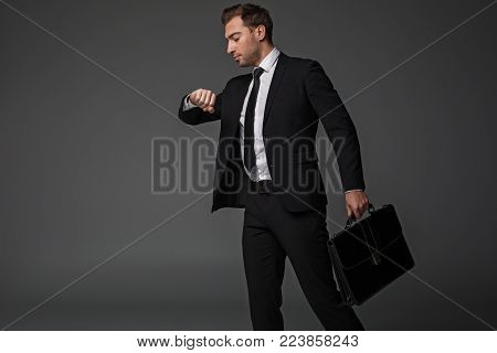 Side view serene worker looking at watch while going at job. He keeping suitcase in arm. Profession concept. Isolated and copy space