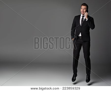 Full length portrait of happy male in suit telling by phone. Conversation and work concept. Copy space