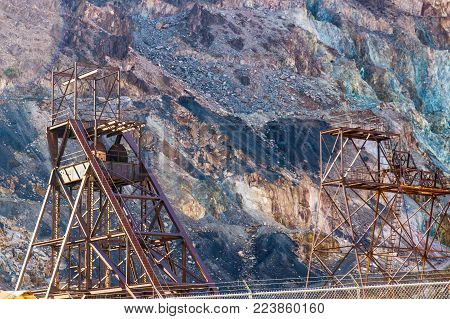 Two Rusty Iron Towers At Base Of Mountain