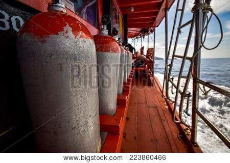 Compressed air tanks preparing for diving trip on wooden boat