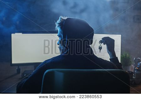 Computer burglar downloading information from digital device while situating at desk. He turning back to camera. Theft concept