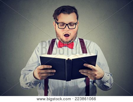 Amazed chubby man in glasses standing and reading interesting book.