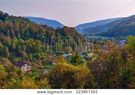 Landscape of Plastunka village in the valley and mountains with varicolored trees in sunny autumn day, Sochi, Russia