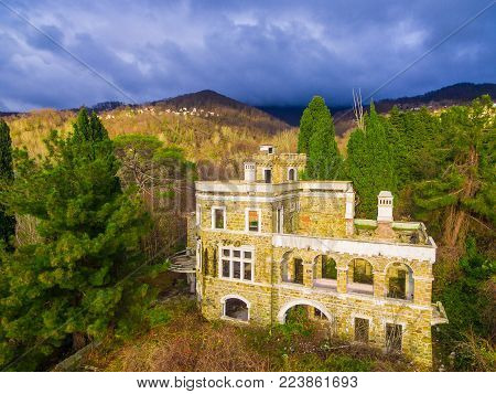 Drone view of the abandoned old mansion called Dacha Kvitko and mountains in the rays of the setting sun, Sochi, Russia