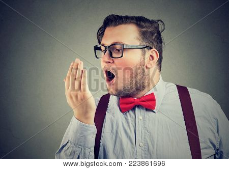 Bearded chubby man in glasses breathing on arm for breath test.
