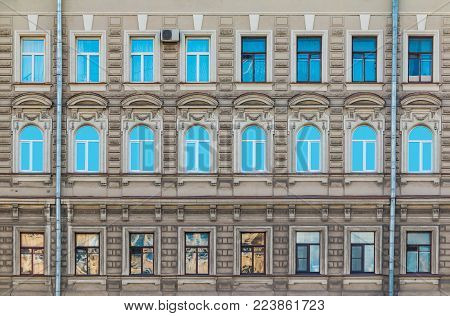 Many windows in a row on the facade of the urban historic building front view, Saint Petersburg, Russia