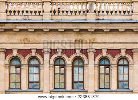 Several windows in a row and balustrade on the facade of the urban historic building front view, Saint Petersburg, Russia